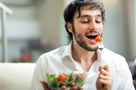 Photo for Young man eating a healthy salad - Royalty Free Image