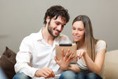 Happy couple looking a tablet on a sofa