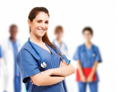 Photo pour Portrait d'une jeune infirmière souriante devant son équipe - image libre de droit