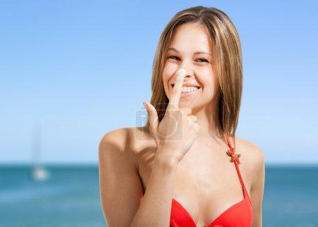 Photo pour Femme appliquant de la crème solaire sur son nez - image libre de droit