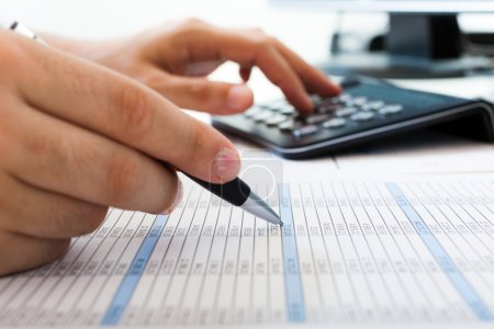 Photo for Accountant checking numbers on a document - Royalty Free Image