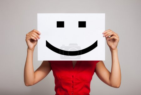Photo for Woman holding a smiling face emoticon - Royalty Free Image