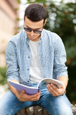 Photo pour Carnet de lecture étudiant masculin dans le parc - image libre de droit