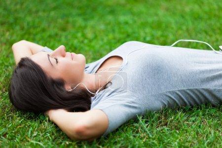 Photo pour Femme se détendre sur l'herbe tout en écoutant de la musique - image libre de droit