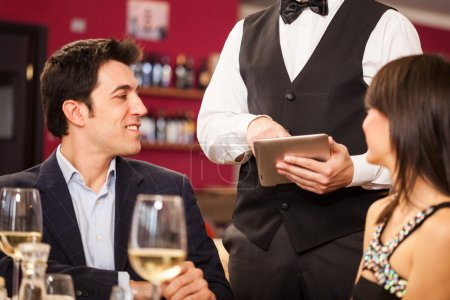 Photo for Waiter using a digital tablet to take an order - Royalty Free Image