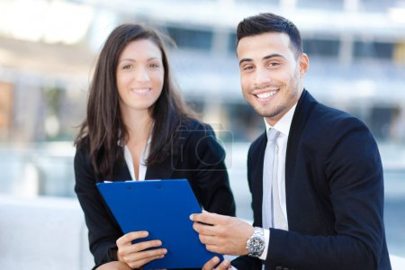 Businessman and businesswoman with a clipboard