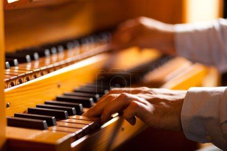 Photo pour Détail d'un homme jouant d'un orgue de l'église - image libre de droit