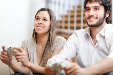 Photo for Young couple playing video games in their apartment - Royalty Free Image
