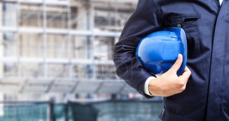 Photo for Detail of a worker holding his helmet in front of a construction site - Royalty Free Image