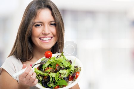Photo for Young woman eating a healthy salad - Royalty Free Image