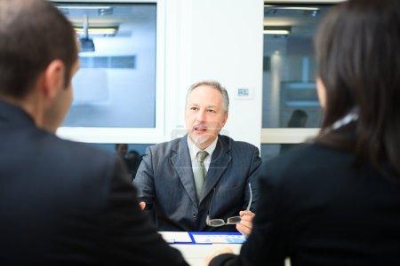 Photo pour Homme d'affaires, parler à un couple dans un bureau - image libre de droit