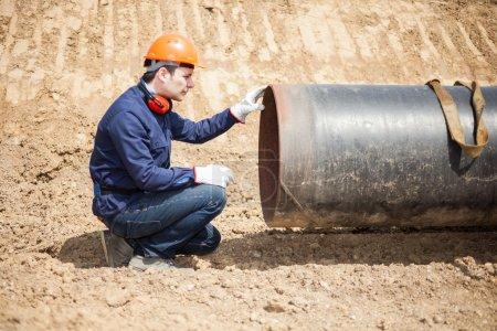Photo pour Homme examinant un tuyau dans un chantier de construction - image libre de droit