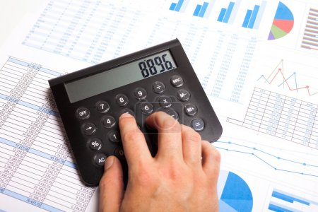 Photo for Businessman examining financial charts using a calculator - Royalty Free Image