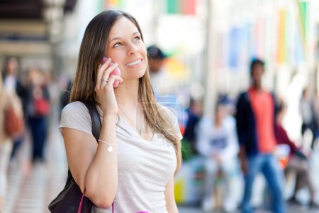 Photo for Beautiful woman on the phone in a crowded city street - Royalty Free Image