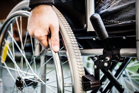 homme à l'aide de son fauteuil roulant
