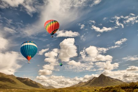 Photo pour Trois montgolfières survolant la nature sauvage des montagnes au Canada avec des nuages gonflés et un ciel bleu . - image libre de droit