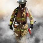 A firefighter pierces through a wall of smoke sear...