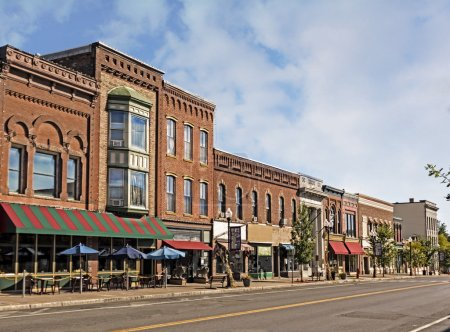 Photo for A photo of a typical small town main street in the United States of America. Features old brick buildings with specialty shops and restaurants. Decorated with autumn decor. - Royalty Free Image