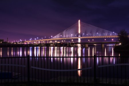 Photo for Night view of the Veterans' Glass City Skyway bridge in Toledo Ohio. The bridges center pylon is lit up with LED lighting and the stainless steel cables are lit with floodlights. - Royalty Free Image