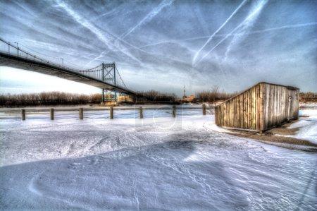 Photo pour Une vue sur le pont suspendu de haut niveau du centre-ville de Toledo Ohio alors qu'il traverse le Maumme rver gelé. Un vieux mouillage de navire est vu au premier plan. Un beau ciel bleu partiellement nuageux fait une jolie scène d'hiver . - image libre de droit