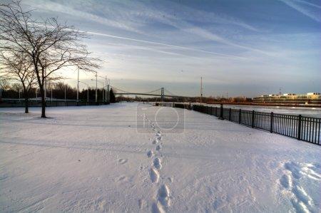Photo pour Une vue sur le pont suspendu de haut niveau du centre-ville de Toledo Ohio alors qu'il traverse le Maumme rver gelé. Un beau ciel bleu partiellement nuageux fait une jolie scène d'hiver . - image libre de droit