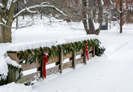 Photo for Winter scene with a snow covered decorative wooden fence with evergreen pine trim and red bows and ribbons. - Royalty Free Image
