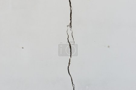 Cracks on solid white painted concrete wall