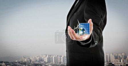 Foto de El hombre de negocios tiene Energía Alternativa (célula solar, tierra, turbina eólica) Elementos de esta imagen proporcionados por la NASA - Imagen libre de derechos