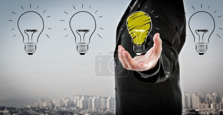 Photo for Business man holding light bulb in his hand - Royalty Free Image