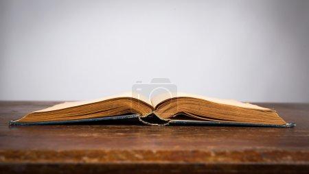 Foto de Abrir el viejo libro vintage en mesa de madera - Imagen libre de derechos