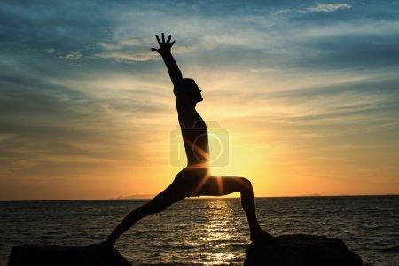 Man act yoga on rock
