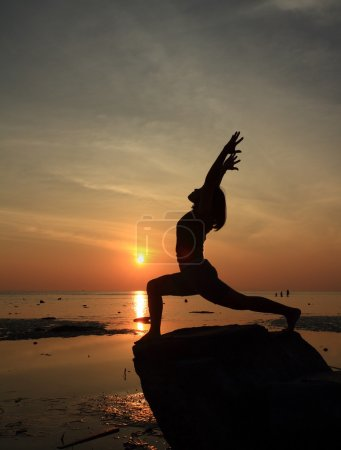 Silhouette yoga girl by the beach at sunrise doing High Lunge Pose