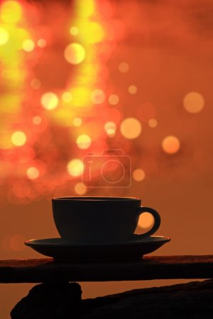 Morning coffe cup on wooden board with bokeh background