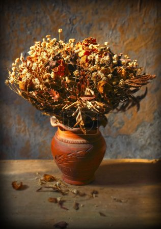 Still life with bouquet of dried roses in clay vase with grunge