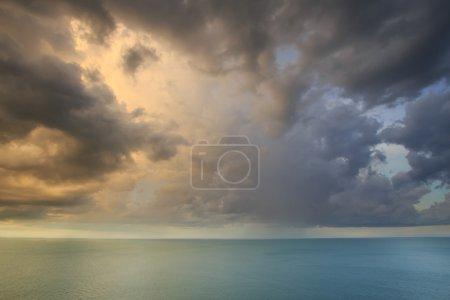 Dramatic tropical rain cloud sky and sea at dusk