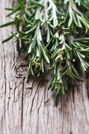 Photo for Bunch of fresh rosemary on a wooden background, - Royalty Free Image