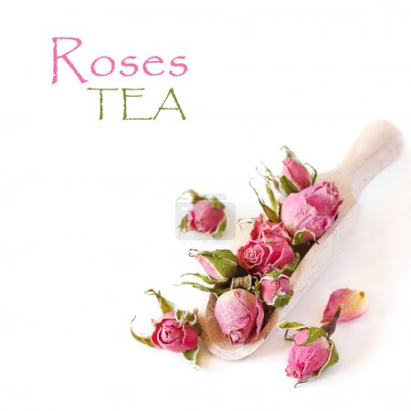 Photo for Roses flowers tea in a wooden scoop on a white background. - Royalty Free Image