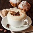 Cup of cappuccino and cake on a dark background cl...