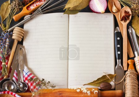 Photo for Open recipe book surrounded of food ingredients and kitchen utensils. - Royalty Free Image