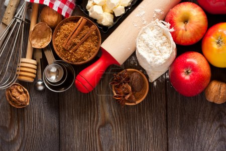 Photo for Ingredients for apple pie cooking. Fresh red apple, butter, flour, brown sugar, nuts and spices on a rustic wooden background. - Royalty Free Image
