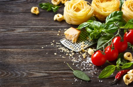 Photo for Italian food ingredients for cooking pasta on a wooden background with copy space. - Royalty Free Image