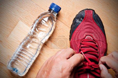 Photo pour Jogger à la maison, attachant ses baskets avec une bouteille d'eau à proximité - image libre de droit