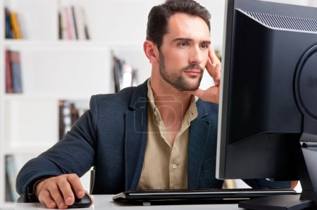 Photo for Man looking at a computer screen, thinking about the job at hand - Royalty Free Image