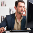 Man looking at a computer screen, thinking about t...
