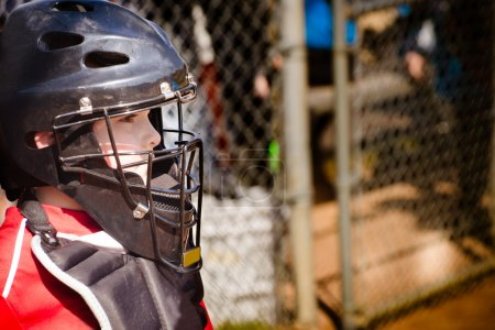 Child playing catcher during baseball game with space for copy