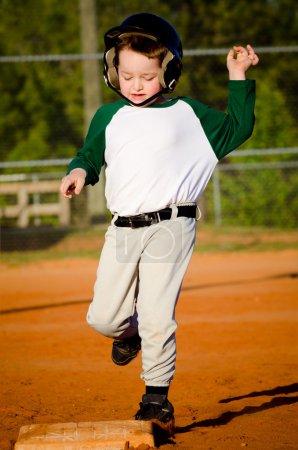Photo pour Jeune enfant exécute les bases tout en jouant au baseball - image libre de droit