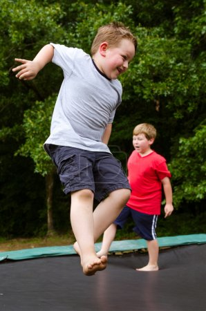 Child playing while jumping on trampoline outdoors on spring day
