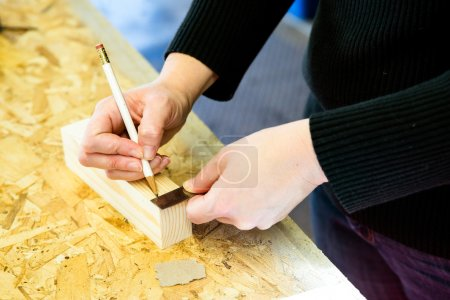 Parent draws stencil on wood block to be used as body for Pinewood Derby car