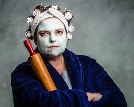 Photo for Mean and ugly housewife with facial mask, hair rollers and rolling pin - Royalty Free Image