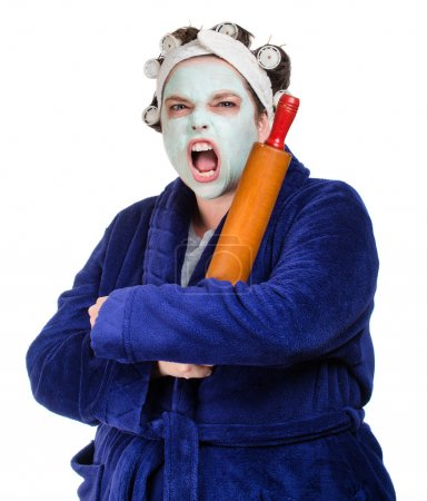 Photo for Mean and ugly housewife with facial mask, hair rollers and rolling pin isolated on white - Royalty Free Image